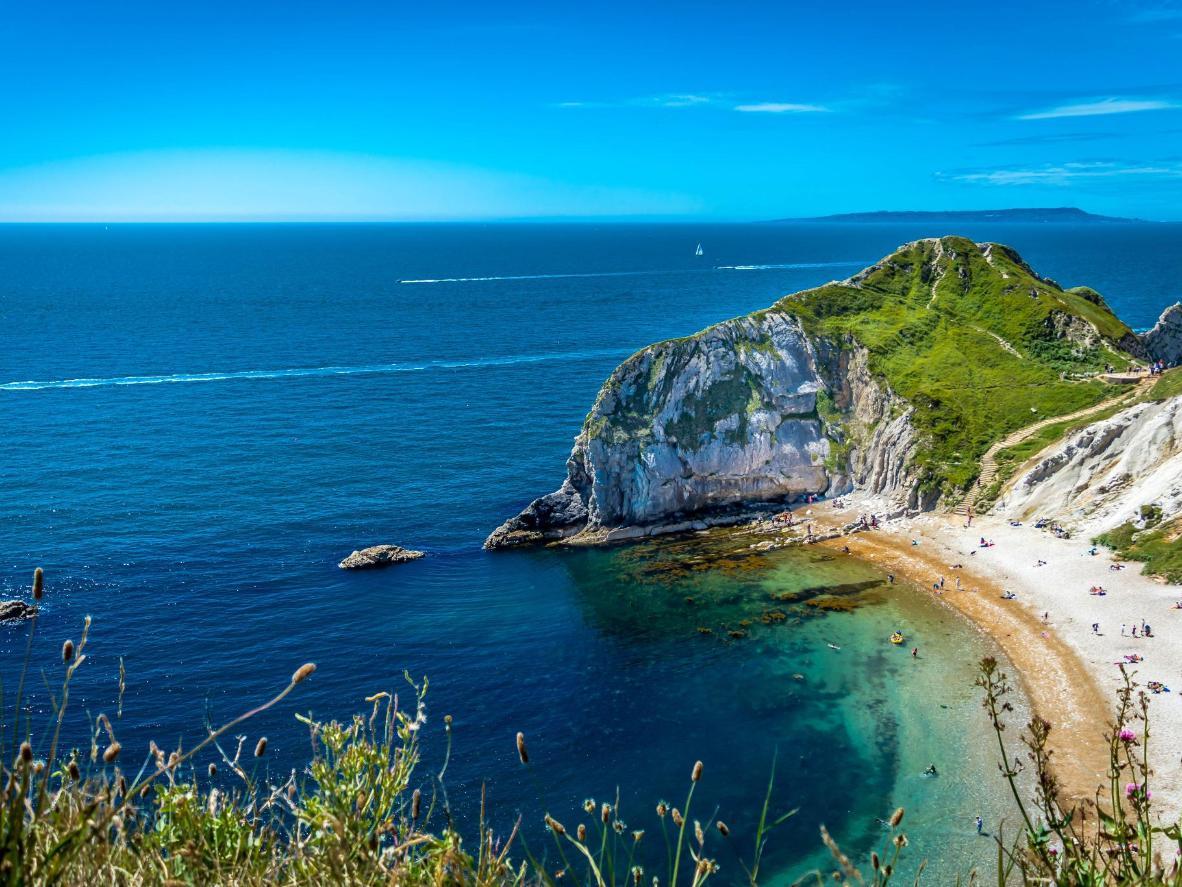Rustige turquoise golfjes kabbelen tegen dit strand in Dorset