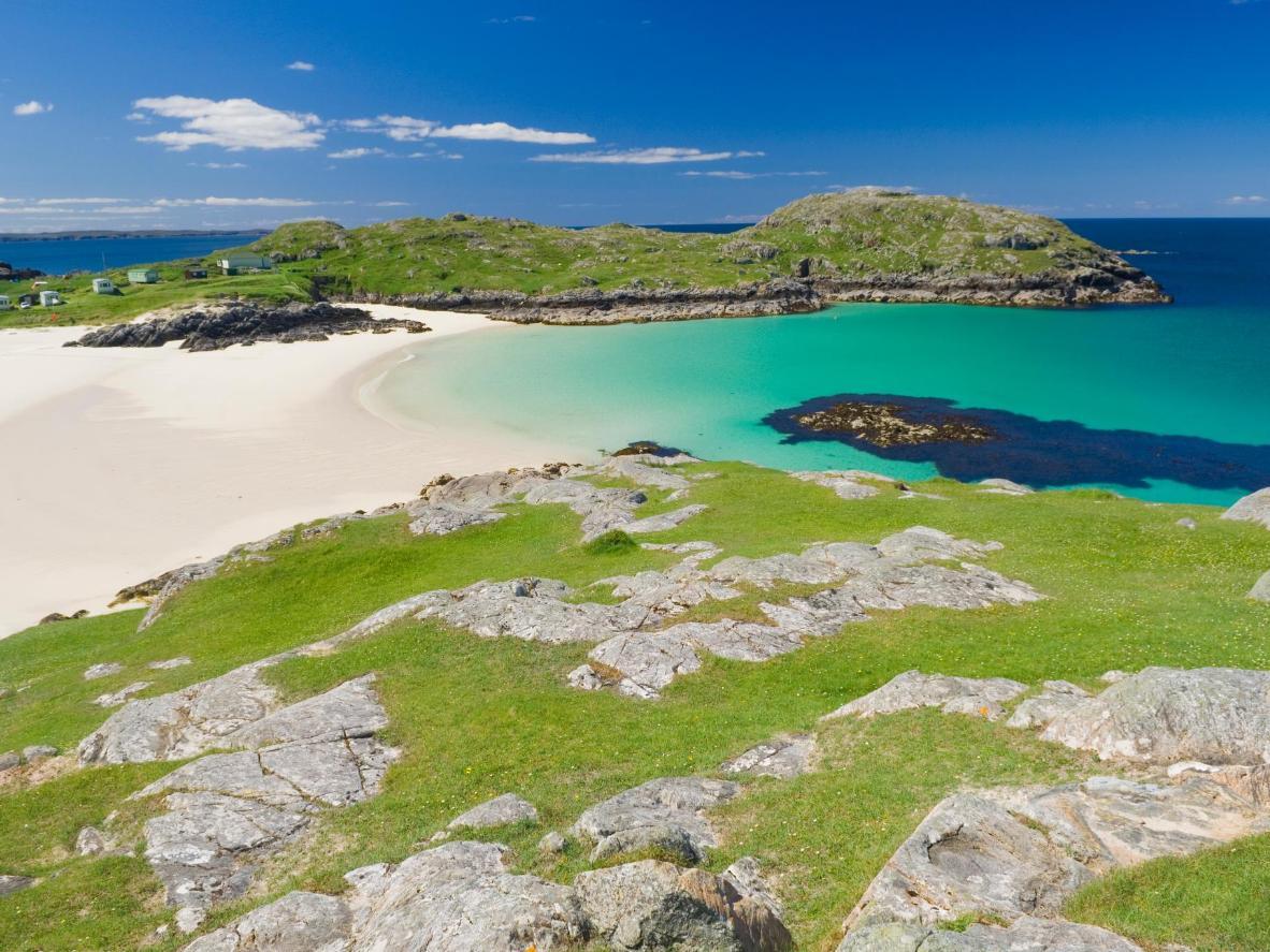 Ontdek parelwit zand, blauwe zee en nieuwsgierige bruinvissen in de Schotse Hooglanden