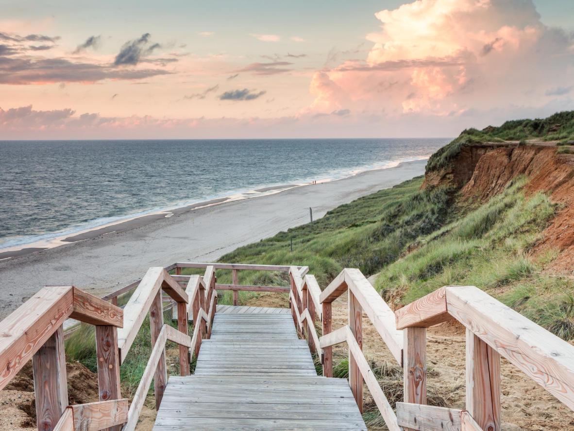 Steigen Sie die Holztreppe am Roten Kliff hinunter zum Strand