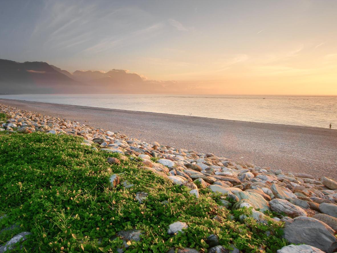 Genießen Sie den Sonnenuntergang über der Sunrise Crescent Bay am Qixingtan