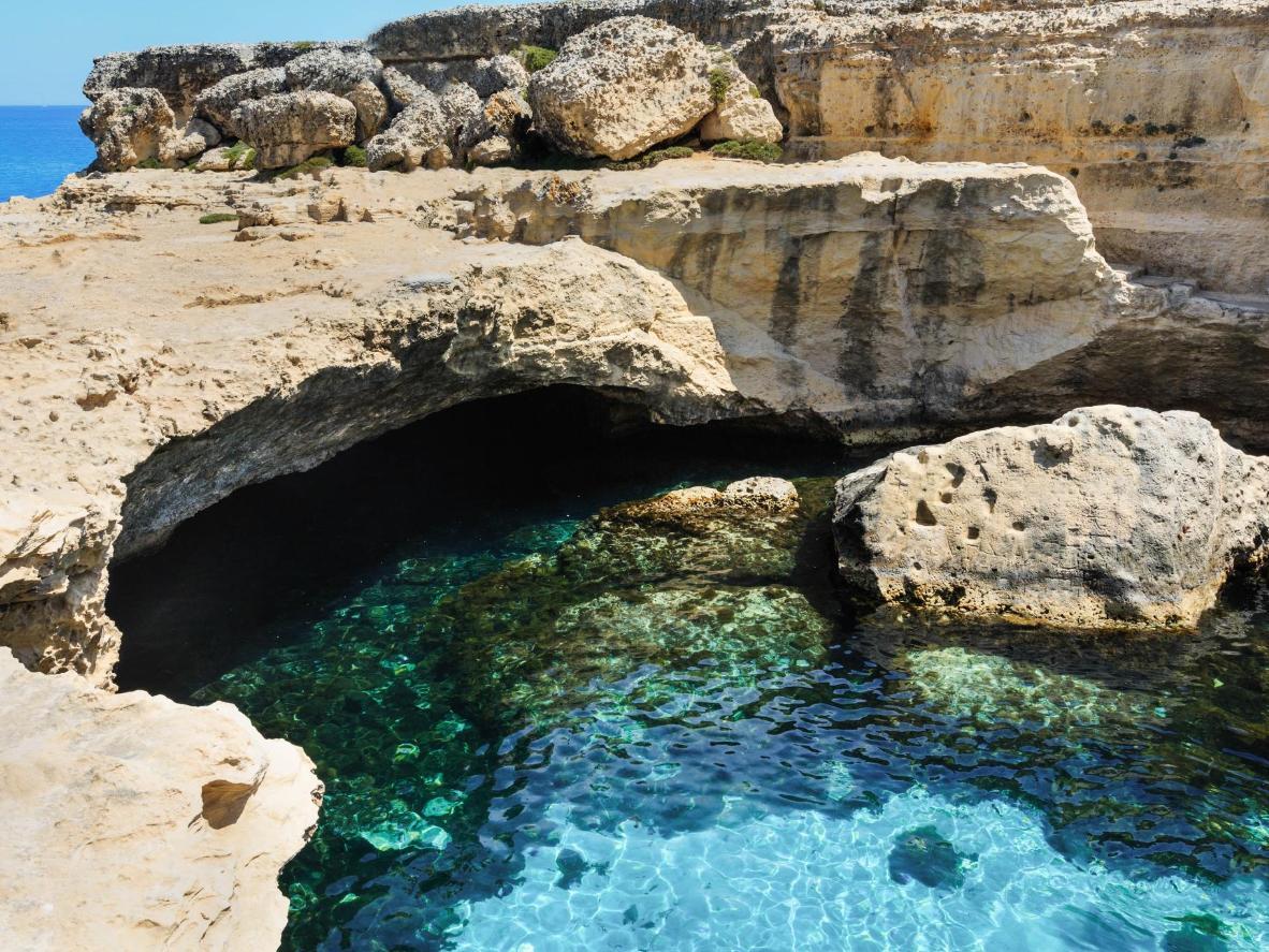 Nuota nelle acque cristalline delle grotte di San Foca