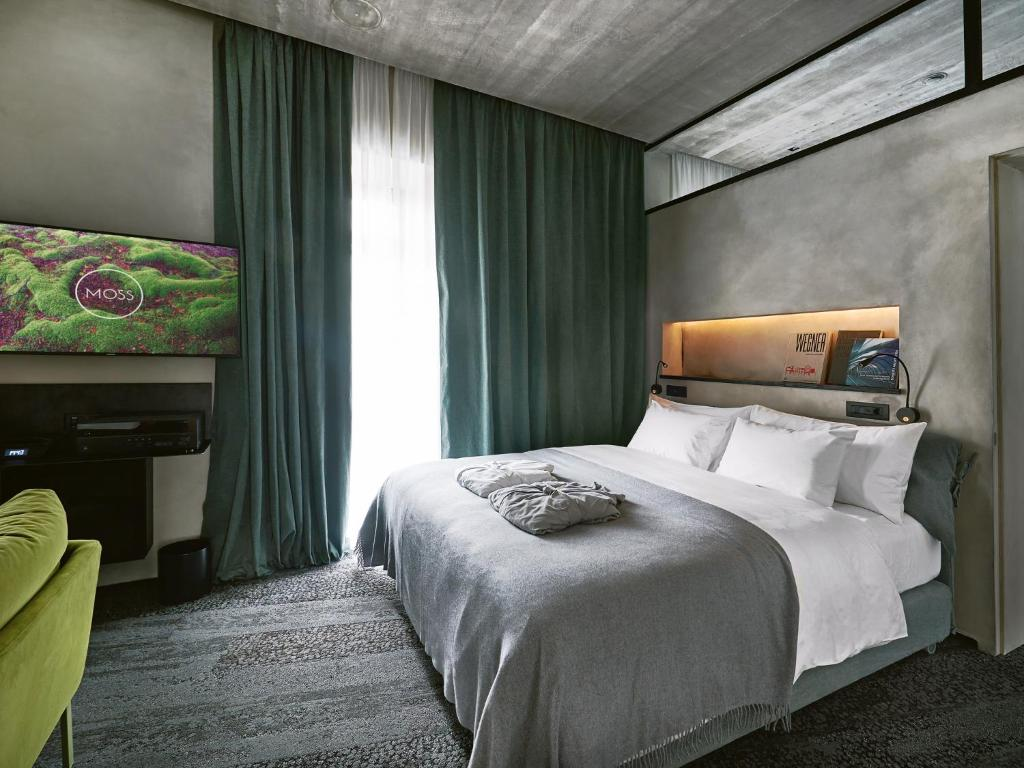 A bed or beds in a room at Moss Boutique Hotel