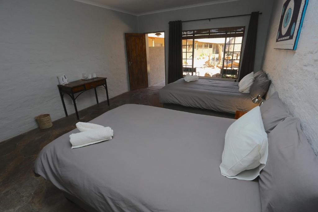 A bed or beds in a room at Solitaire Lodge
