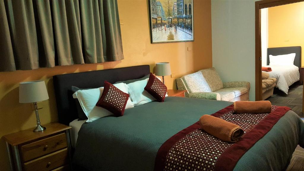 A bed or beds in a room at New Olympic Motel