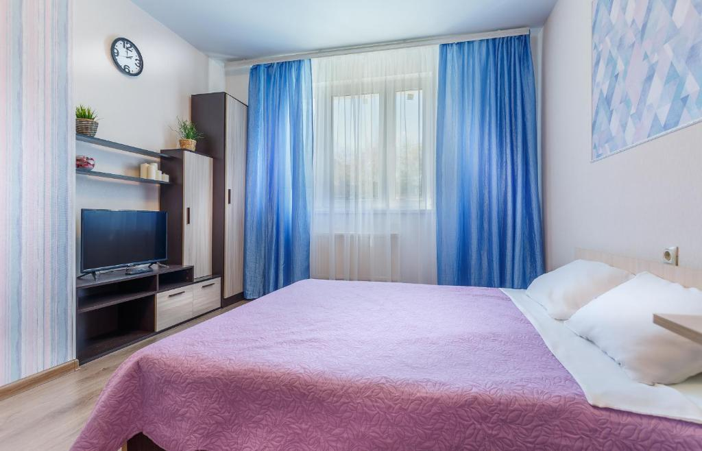 A bed or beds in a room at Apartment on Strelkovaya 6