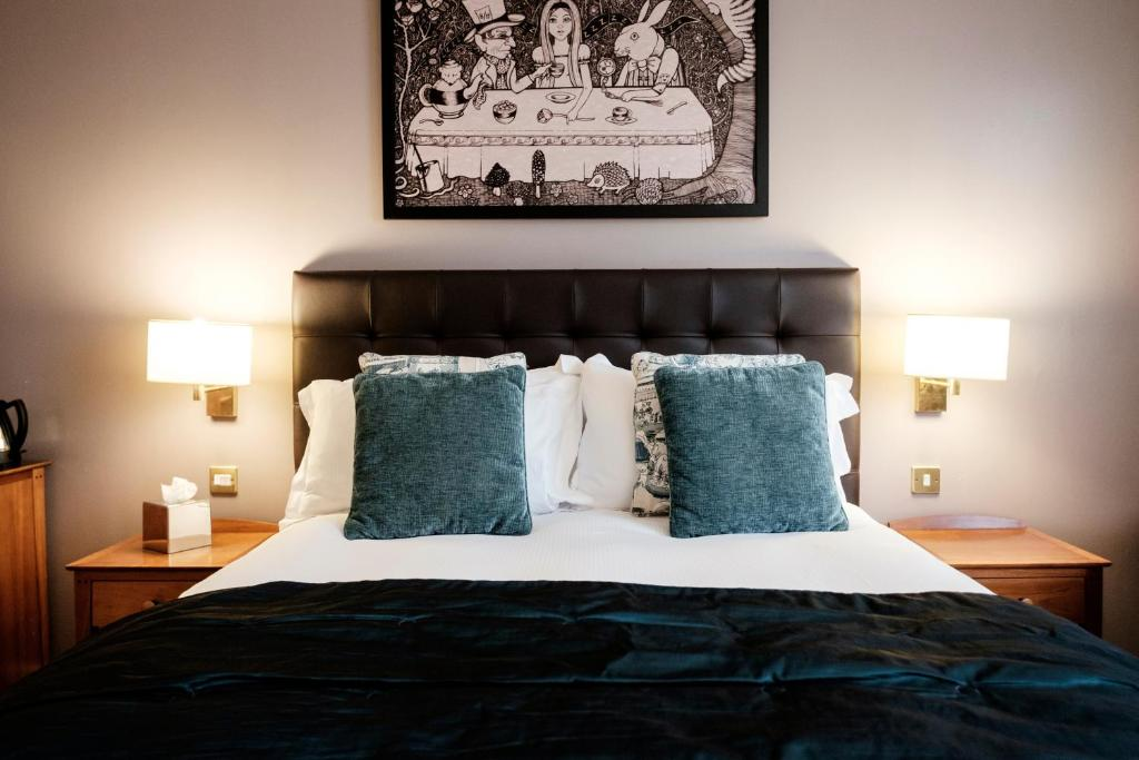A bed or beds in a room at The Mad Hatter Hotel