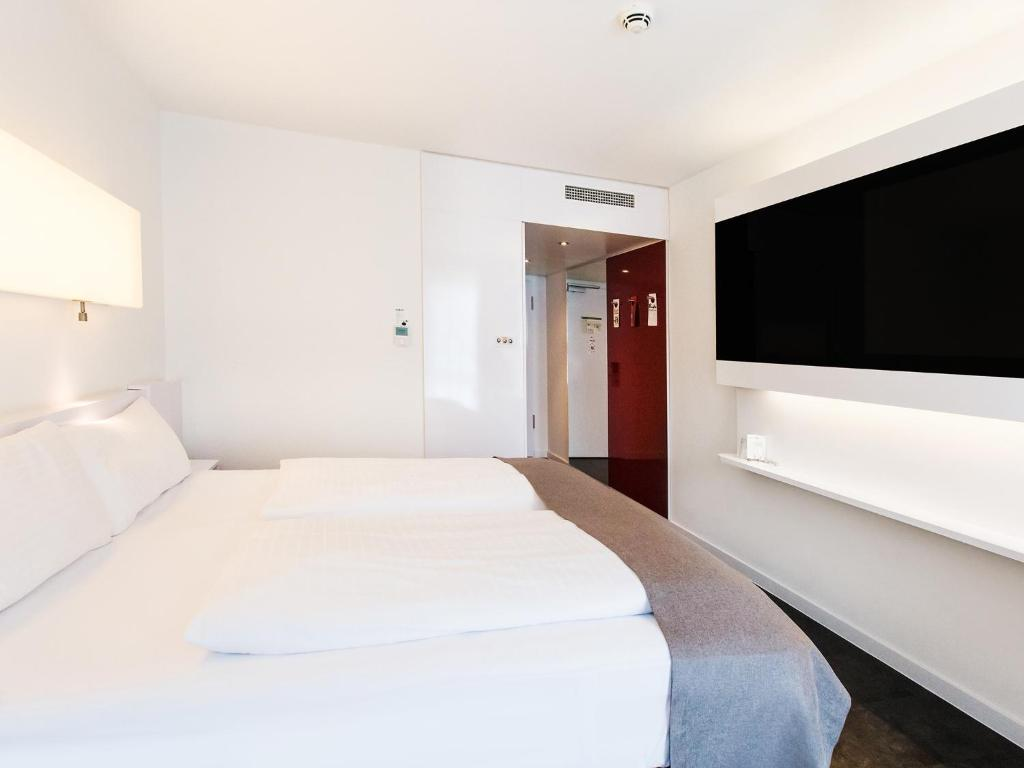 A bed or beds in a room at DORMERO Hotel Frankfurt