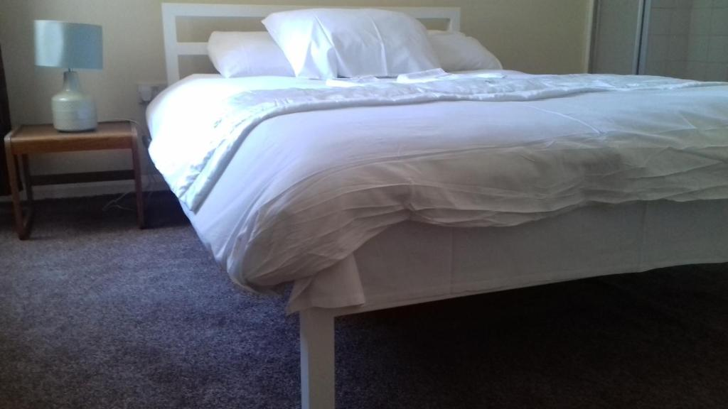 A bed or beds in a room at Haven House Hotel