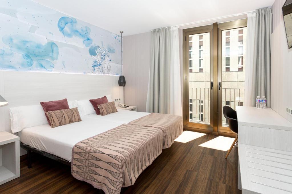 Säng eller sängar i ett rum på Hostal Operaramblas