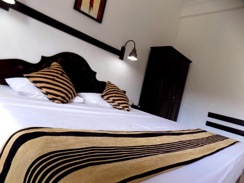 A bed or beds in a room at Kandyan Arts Residency