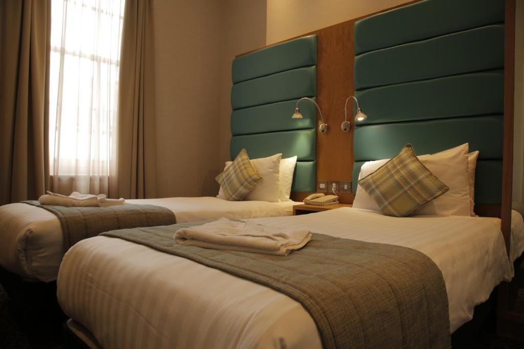 A bed or beds in a room at Astors Belgravia