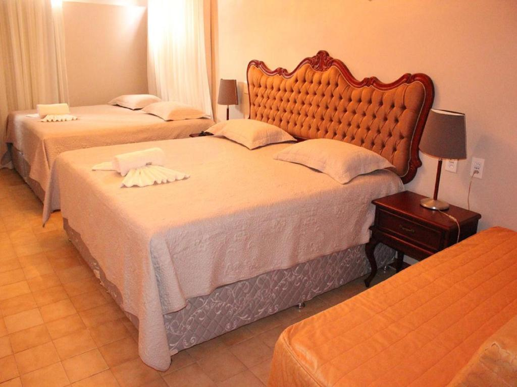A bed or beds in a room at Seringal Hotel