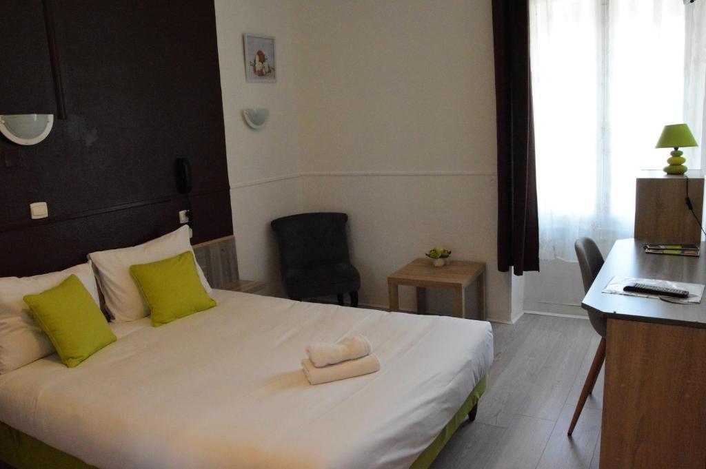 A bed or beds in a room at Hôtel de la Colombière