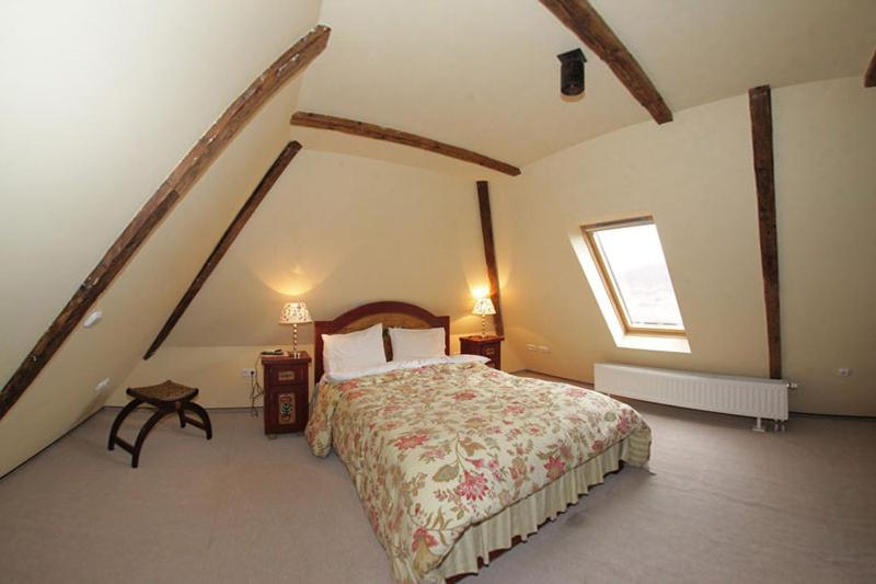 A bed or beds in a room at Pensiune Citadela Sighisoara