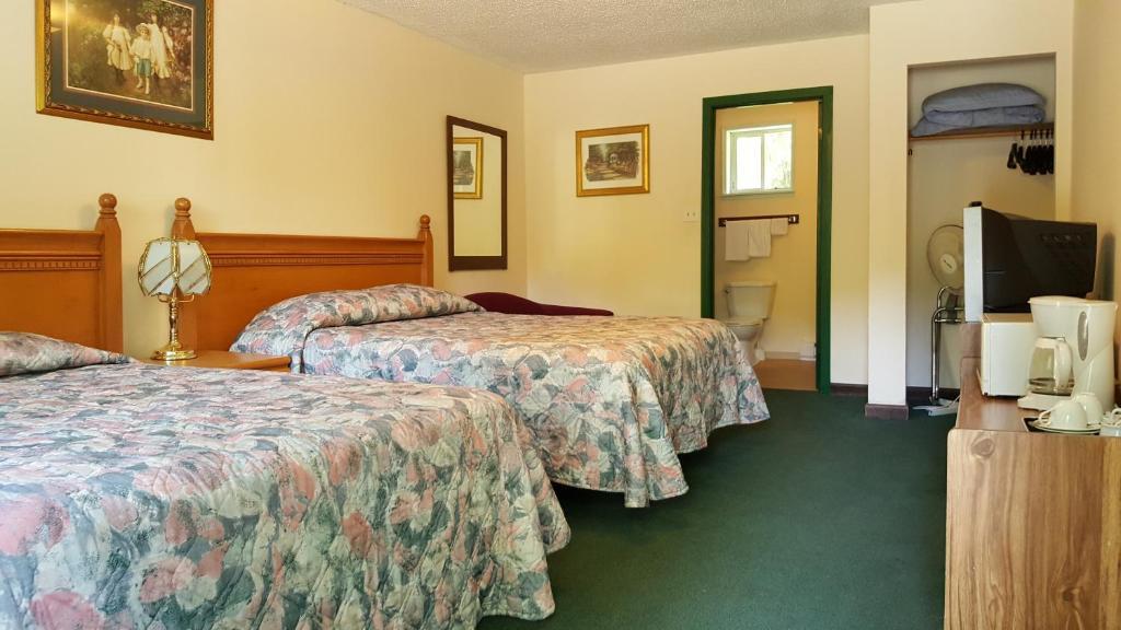 A bed or beds in a room at Pathfinder Motel & R.V. Park