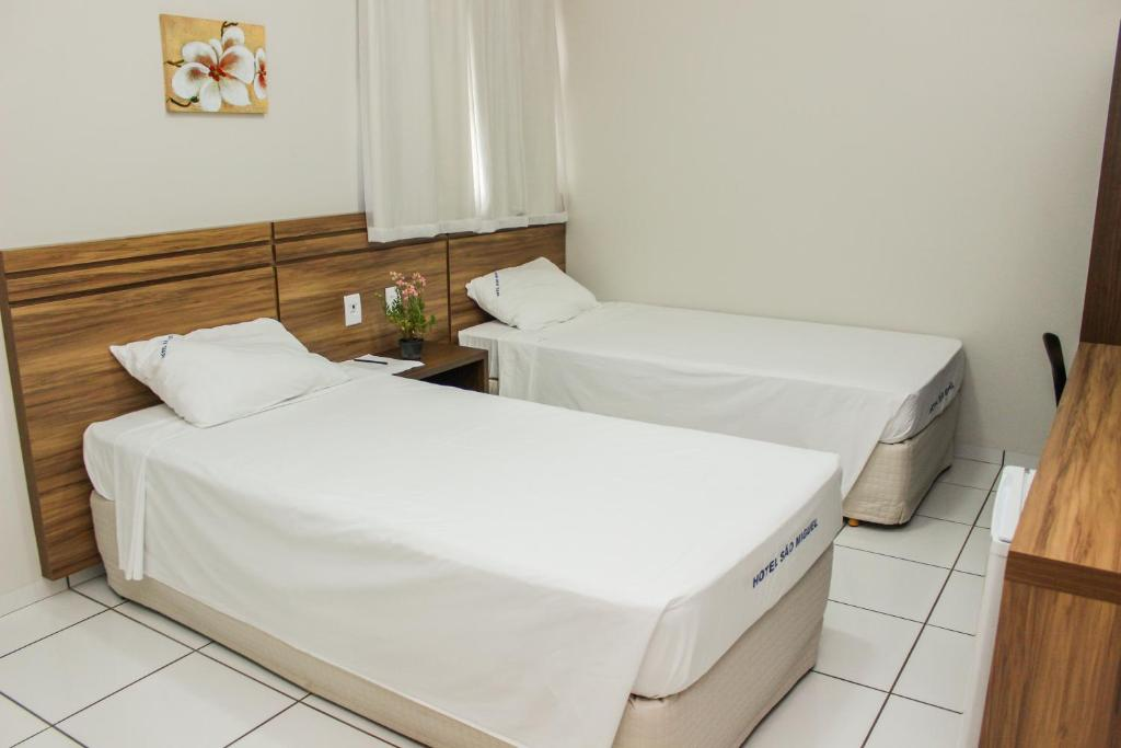 A bed or beds in a room at Hotel São Miguel