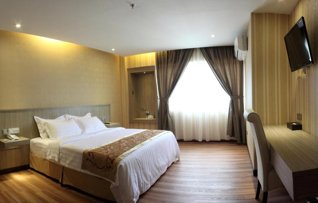 A bed or beds in a room at Mandarin Hotel Kota Kinabalu