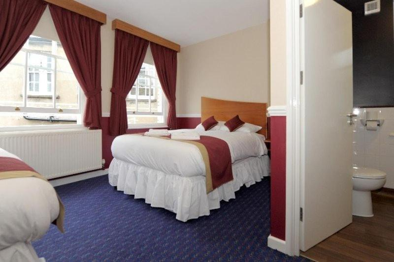 A bed or beds in a room at The Queen's Hotel Wetherspoon