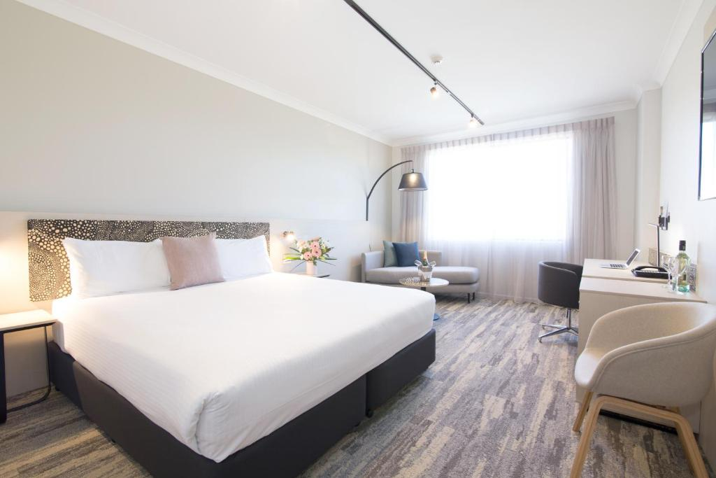 A bed or beds in a room at Mermaid Waters Hotel by Nightcap Plus