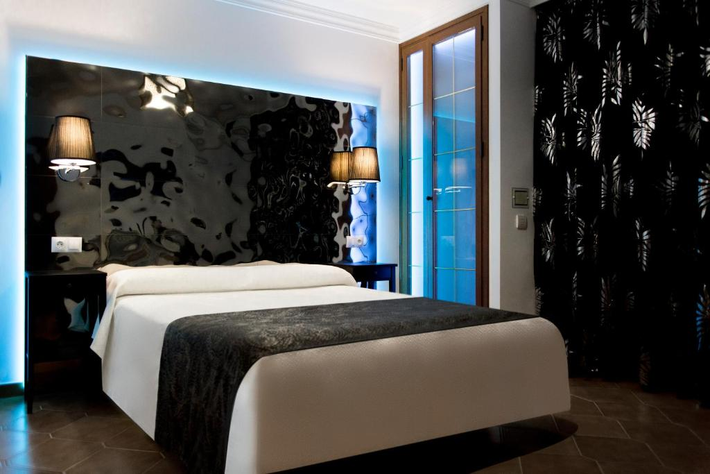 A bed or beds in a room at Hostal Alhambra - Adults Only