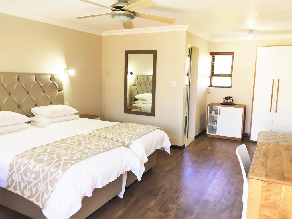 A bed or beds in a room at Loerie Guest Lodge