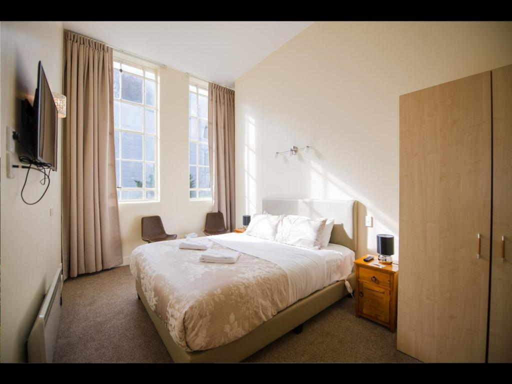 A bed or beds in a room at Grand Central Serviced Apartments