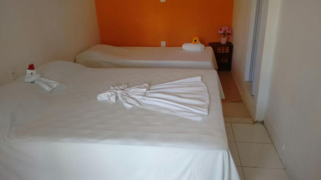 A bed or beds in a room at Pousada Mangueira