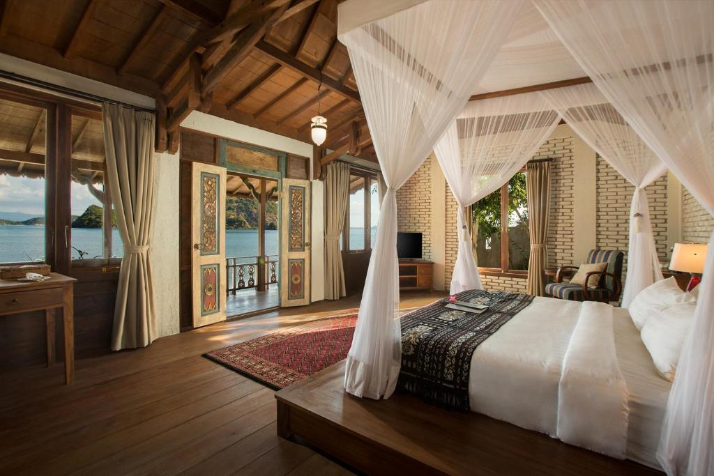 A bed or beds in a room at Plataran Komodo Beach Resort