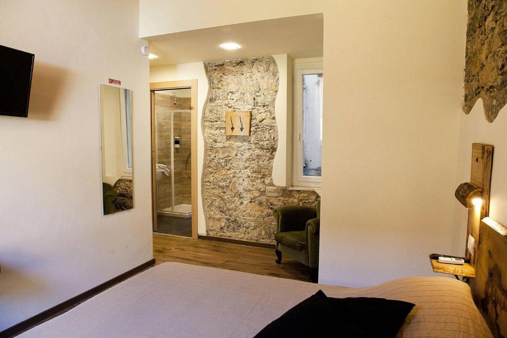 A bed or beds in a room at La Taverna del Metallo Rooms