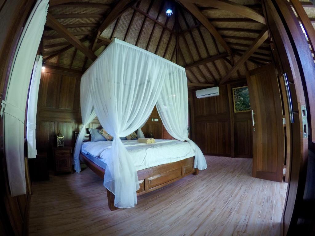 سرير أو أسرّة في غرفة في Pondok Seken Wooden Villa