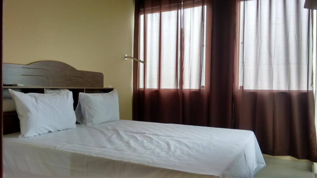 A bed or beds in a room at Hotel Mourão