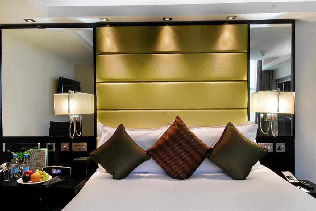 A bed or beds in a room at The Barbican Rooms