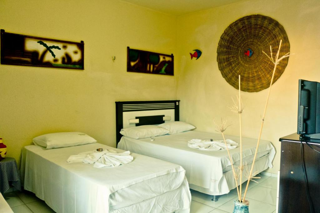 A bed or beds in a room at Hotel Pousada Maria Brasil