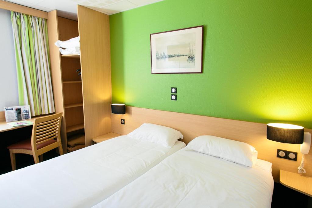 A bed or beds in a room at Hôtel Vert