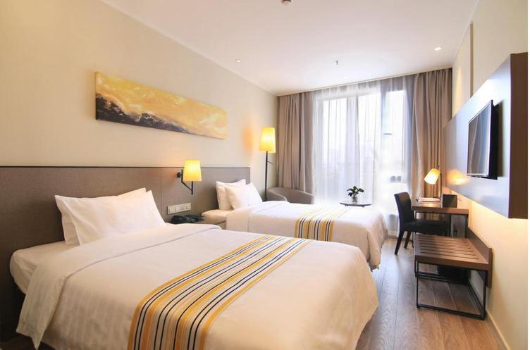 A bed or beds in a room at Homeinn Hotel Boutique Shanghai Pudong Airport Branch