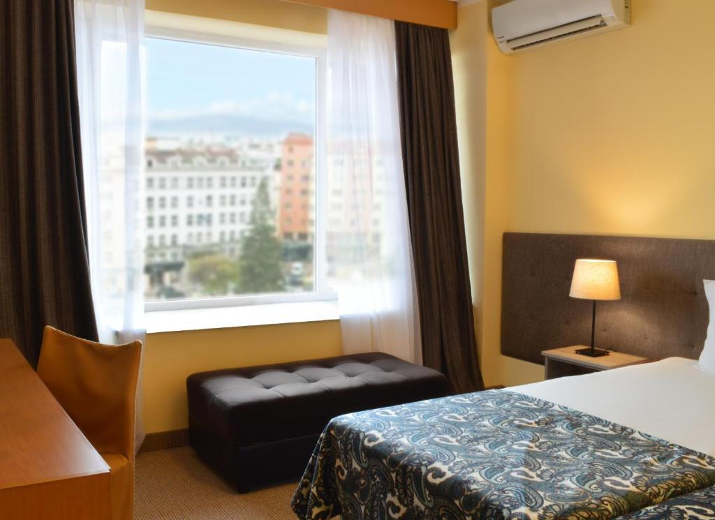A bed or beds in a room at Rila Hotel Sofia