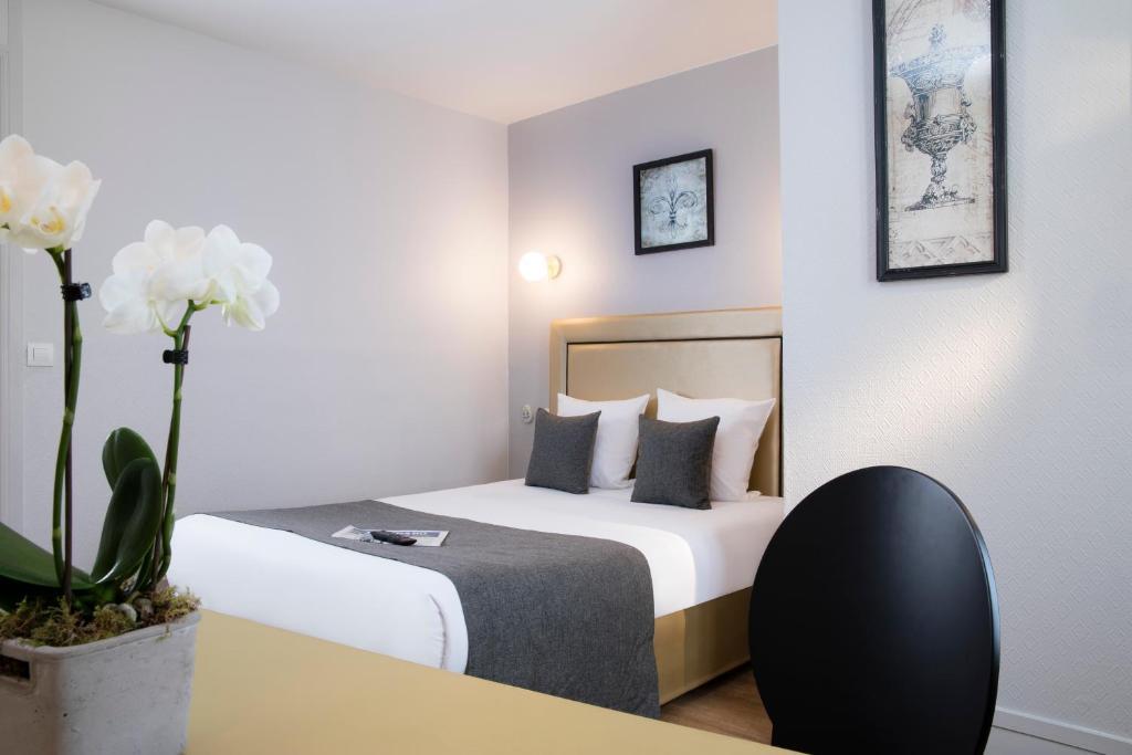 A bed or beds in a room at A l'Hôtel Des Roys