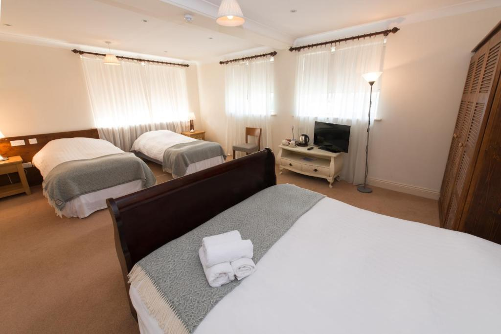 A bed or beds in a room at Connemara Lake Hotel