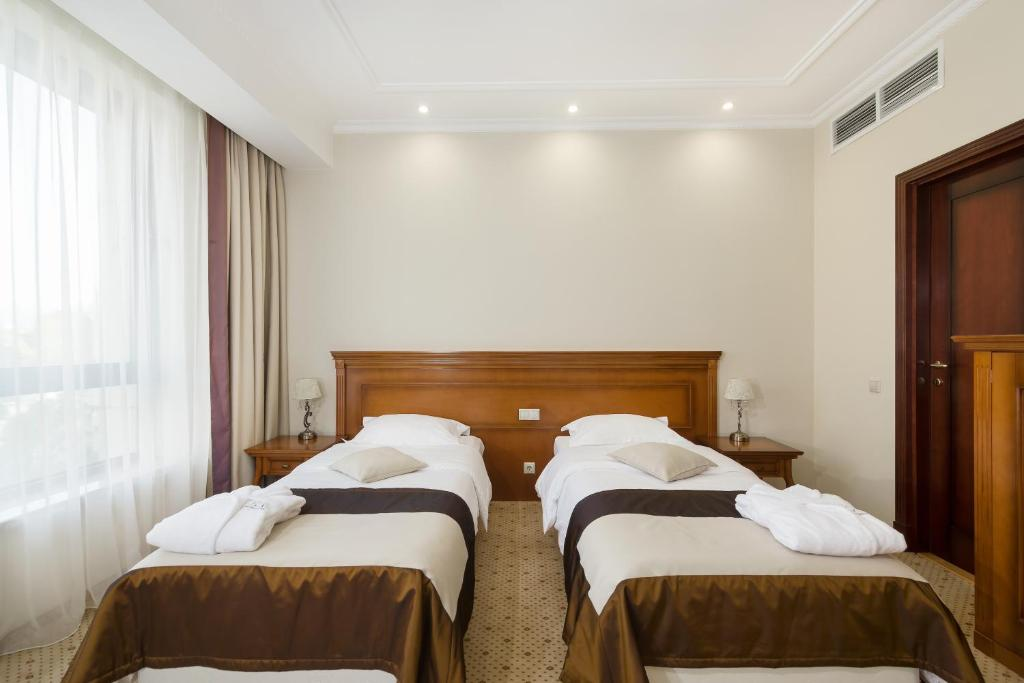 A bed or beds in a room at Звездный Отель WELLNESS & SPA