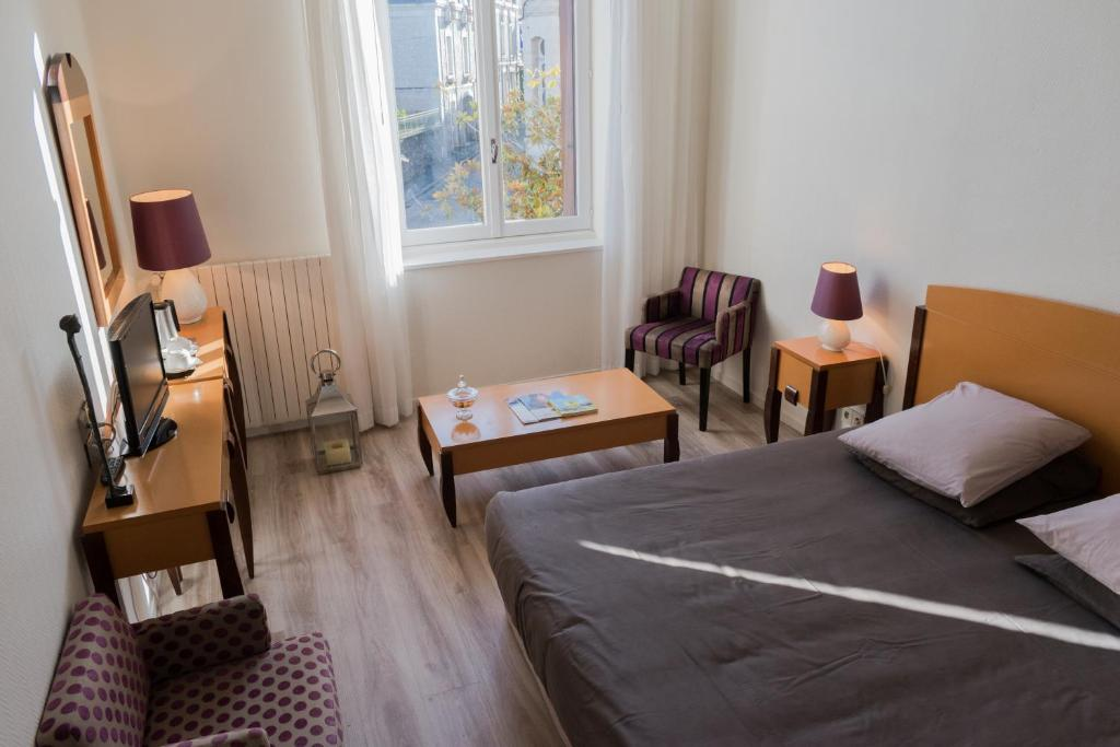 A bed or beds in a room at Logis Hotel Saint-Roch