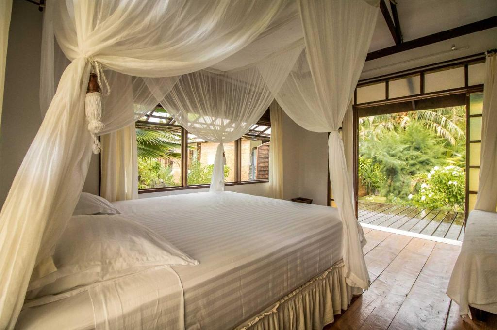 A bed or beds in a room at Le Coconut Lodge