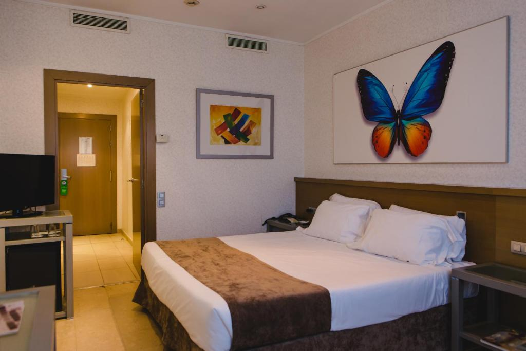 A bed or beds in a room at Hotel Mas Camarena