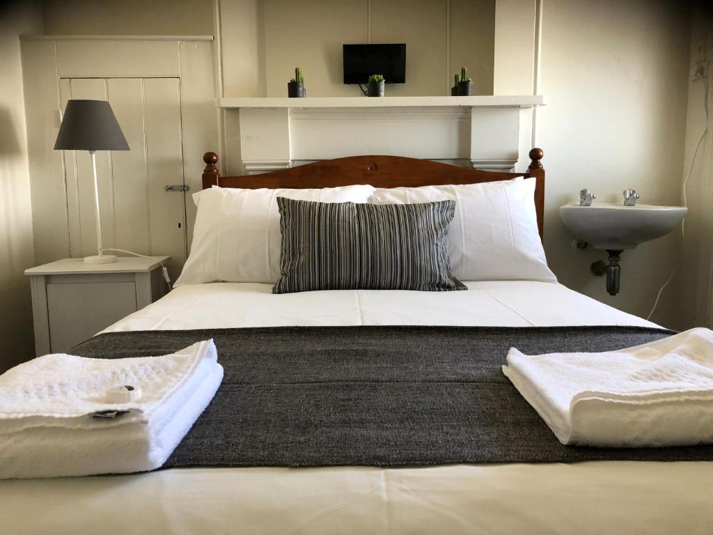 A bed or beds in a room at Cornwall Hotel
