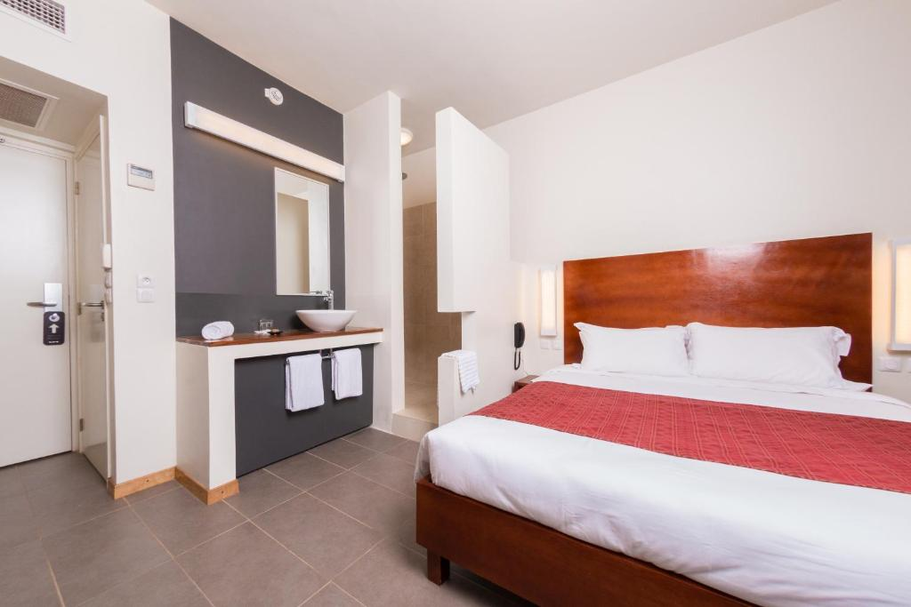 A bed or beds in a room at ONOMO Hotel Bamako