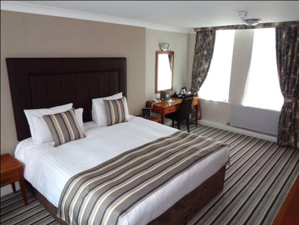 A bed or beds in a room at Aston Court Hotel