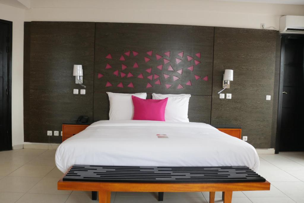 A bed or beds in a room at Douala Design Hotel