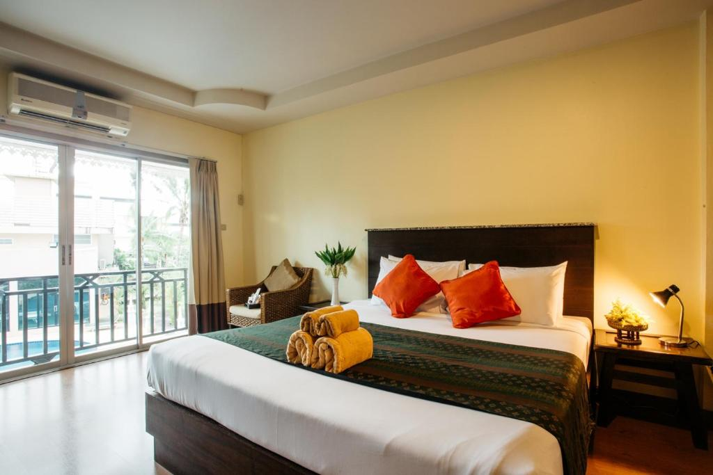 A bed or beds in a room at Diamond Park Inn Chiangrai & Resort