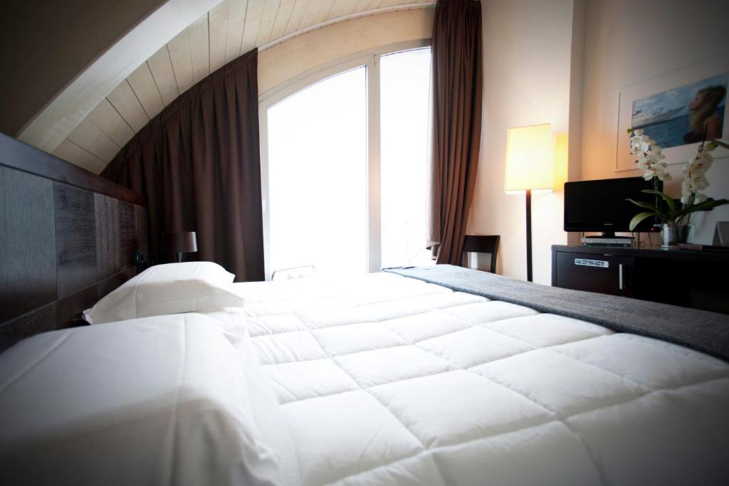 A bed or beds in a room at Hotel Mosaico