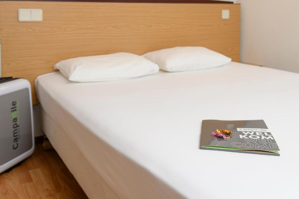 A bed or beds in a room at Campanile Hotel & Restaurant Delft