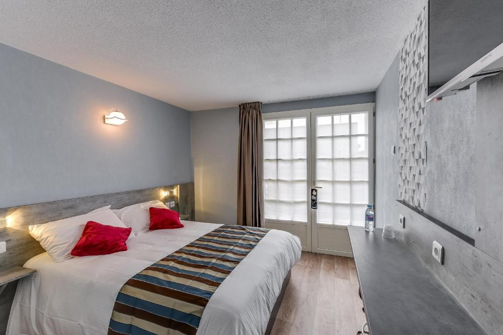A bed or beds in a room at Brit Hotel Confort Thouars